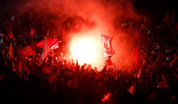 Supporters of the Islamist Ennahda movement light flares and wave flags during a rally in Tunis